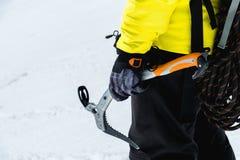 Un uomo dell'alpinista giudica un'ascia di ghiaccio alta nelle montagne coperte di neve Primo piano da dietro all'aperto estremo  Fotografia Stock