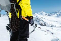 Un uomo dell'alpinista giudica un'ascia di ghiaccio alta nelle montagne coperte di neve Primo piano da dietro all'aperto estremo  Immagini Stock Libere da Diritti
