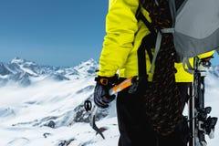 Un uomo dell'alpinista giudica un'ascia di ghiaccio alta nelle montagne coperte di neve Primo piano da dietro all'aperto estremo  Fotografie Stock