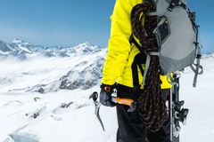 Un uomo dell'alpinista giudica un'ascia di ghiaccio alta nelle montagne coperte di neve Primo piano da dietro all'aperto estremo  Immagini Stock