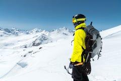 Un uomo dell'alpinista giudica un'ascia di ghiaccio alta nelle montagne coperte di neve Vista dalla parte posteriore all'aperto e Fotografia Stock Libera da Diritti