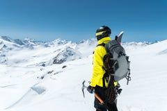 Un uomo dell'alpinista giudica un'ascia di ghiaccio alta nelle montagne coperte di neve Vista dalla parte posteriore all'aperto e Immagini Stock Libere da Diritti