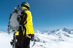 Un uomo dell'alpinista giudica un'ascia di ghiaccio alta nelle montagne coperte di neve Vista dalla parte posteriore all'aperto e Fotografie Stock