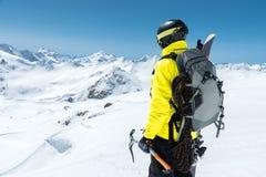 Un uomo dell'alpinista giudica un'ascia di ghiaccio alta nelle montagne coperte di neve Vista dalla parte posteriore all'aperto e Fotografia Stock