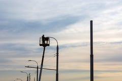 Un uomo dell'elettricista mette una lanterna su un palo, contro il cielo, durante il tramonto immagine stock