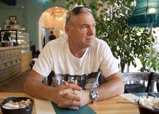 Un uomo dell'età che si siede in un caffè immagine stock