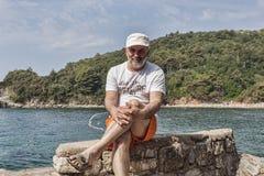 Un uomo dell'età matura si siede sulle rocce che gettano il suo piede sul piede Fotografie Stock Libere da Diritti