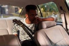 Un uomo della corsa mista in salone dell'automobile, con la chitarra, avendo emozioni Uno studente che ? recente sull'esame di mu fotografia stock libera da diritti