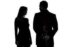 Un uomo delle coppie che nasconde sorridere di rosa della donna del fiore Fotografie Stock