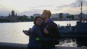 Un uomo delle coppie e una donna amorosi, supporto sulla spiaggia, vicino al fiume nella città e nel bacio Movimento lento 1920x1 video d archivio