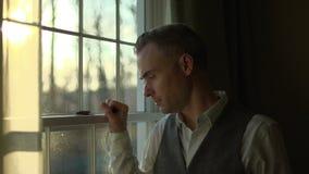 un uomo depresso ad una finestra stock footage