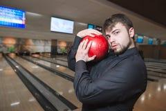 Un uomo di affari che posa su una macchina fotografica con palla da bowling in sue mani Un uomo con una barba gioca un club di bo Fotografia Stock