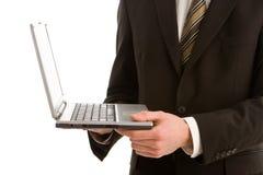 Un uomo di affari che tiene un computer portatile d'argento immagini stock libere da diritti