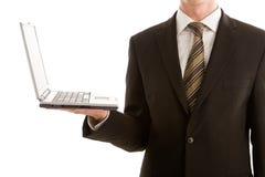 Un uomo di affari che tiene un computer portatile d'argento fotografia stock