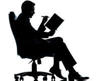 Un uomo di affari con l'ordine del giorno che cattura seduta delle note Immagini Stock Libere da Diritti