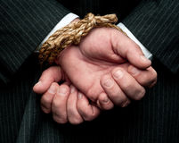 Un uomo di affari con le sue mani legate dietro la parte posteriore di hs Fotografie Stock Libere da Diritti