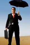 Un uomo di affari con una cartella e un ombrello Immagini Stock Libere da Diritti