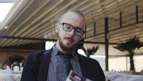 Un uomo di affari in vetri con una barba colpisce una rivista archivi video