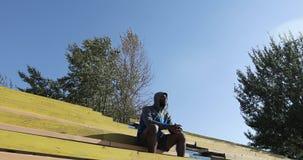 Un uomo di colore si siede in uno stadio archivi video