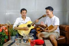 Un uomo di due amici che gioca gli strumenti musicali fotografia stock