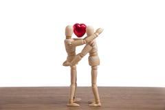 Un uomo di legno della bambola in una manifestazione di tema del biglietto di S. Valentino il suo amore alle sue coppie fotografie stock libere da diritti