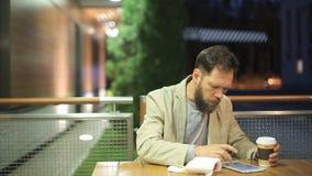 Un uomo di mezza età barbuto dell'aspetto caucasico sta sedendosi ad una tavola in un caffè dell'estate nella sera, guardare archivi video