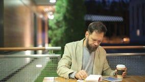 Un uomo di mezza età barbuto dell'aspetto caucasico sta sedendosi ad una tavola in un caffè dell'estate nella sera, guardare video d archivio