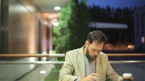 Un uomo di mezza età barbuto dell'aspetto caucasico sta sedendosi ad una tavola in un caffè dell'estate nella sera, guardare stock footage