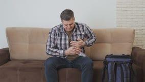 Un uomo di mezza età, sedentesi sullo strato, tiene la sua mano nella regione del cuore, ritenente il dolore acuto archivi video