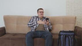 Un uomo di mezza età, sedentesi sullo strato, tiene la sua mano nella regione del cuore, ritenente il dolore acuto Un uomo chiama video d archivio