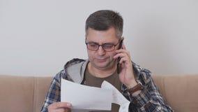 Un uomo di mezza età si siede su un sofà in una camera di albergo e nei colloqui sul telefono, tenente un documento cartaceo stock footage