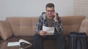 Un uomo di mezza età si siede su un sofà in una camera di albergo ed i colloqui sul telefono, tenendo un documento cartaceo ed ac stock footage