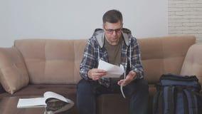 Un uomo di mezza età si siede su un sofà in una camera di albergo ed i colloqui sul telefono, tenendo un documento cartaceo ed ac video d archivio