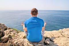 Un uomo di misura nella posizione di Lotus su una spiaggia Giovane uomo di forma fisica che fa yoga all'aperto Immagini Stock