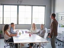 Un uomo dice il suo business plan ad un gruppo di impiegati di concetto immagine stock