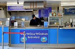 Un uomo dietro il contatore di un negozio della patata fritta e del pesce fotografia stock libera da diritti