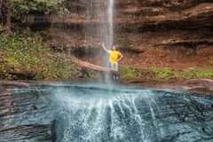 Un uomo dietro il ` di Salto Suizo del ` il più alta cascata del Paraguay Immagine Stock