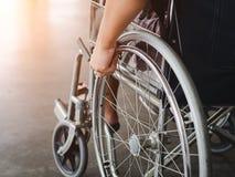Un uomo disabile sta sedendosi in una sedia a rotelle Tiene le sue mani sopra fotografia stock