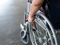 Un uomo disabile sta sedendosi in una sedia a rotelle Tiene le sue mani sopra fotografia stock libera da diritti