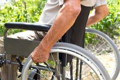 Un uomo disabile sta sedendosi in una sedia a rotelle, tiene le sue mani sulla ruota Concetto della gente di handicap fotografia stock
