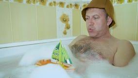 Un uomo divertente con un petto peloso si trova nel bagno e gioca con un yacht del giocattolo dei bambini stock footage