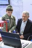 Un uomo e un bambino stanno studiando un programma per lavorare ad un pri 3D Immagini Stock