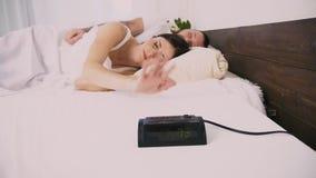 Un uomo e un orologio della donna di mattina suona i risvegli per lavorare archivi video