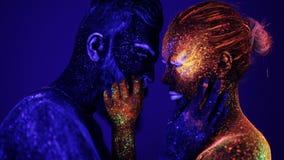 Un uomo e una donna alla luce ultravioletta si accarezzano Fuoco e ghiaccio, due ipostasi video d archivio