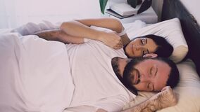 Un uomo e una donna che dormono accanto al marito ed alla moglie video d archivio