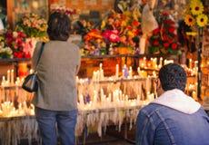 Un uomo e una donna contemplano le candele immagine stock