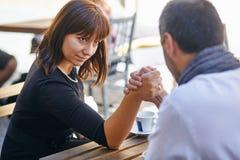 Un uomo e una donna fanno concorrenza sui reslings del braccio fotografie stock