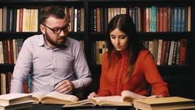 Un uomo e una donna hanno letto i libri nella biblioteca stanno preparando per l'esame video d archivio