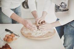 Un uomo e una donna incinta cucinano insieme nella cucina e producono la pasta Tono leggero Nessun fronte immagine stock