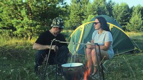 Un uomo e una donna in occhiali da sole stanno sedendo dalla tenda, tè bevente e stanno guardando il vaso appendere sopra il fuoc archivi video